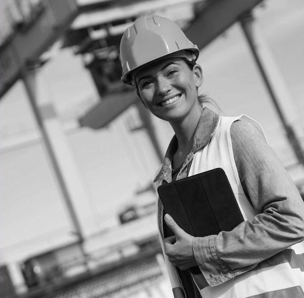 Smiling woman in hard hat with clipboard